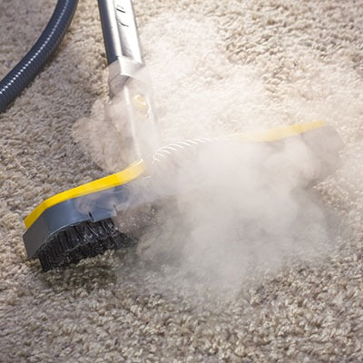 Using dry steam cleaner to sanitize floor carpet