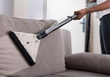 man steam cleaning upholstery couch